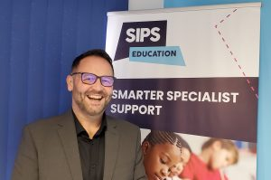 Smiling Brian Cape of SIPS Education standing in front of a pull-up banner which says 'Smarter specialist support'